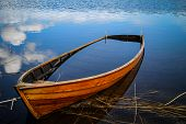 foto of old boat  - Old boat by the lake filled with water - JPG
