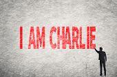 Asian businessman write text on wall, I am Charlie
