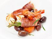 Shrimps with bacon, olives and rosemary on plate