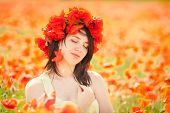 Pregnant happy woman in a flowering poppy field outdoors
