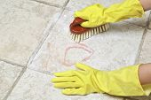 picture of suds  - hands in rubber gloves scrubbing the tiles - JPG