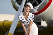 stock photo of starlet  - beautiful navy girl standing in front of a WWII aircraft