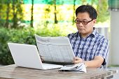 Asian Man Reading The Financial Newspaper With White Laptop.