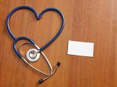 A stethoscope in a shape of heart with a blank lying on a desk