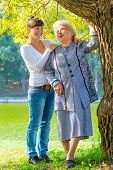 Caring And Loving Granddaughter Walking With Her Grandmother In The Park