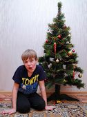 child with funny grimace near christmas tree