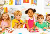 picture of kindergarten  - Large group of happy diverse looking preschool kids boys and girls play with plasticine in class in kindergarten - JPG