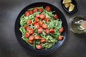 Spaghetti with roasted tomatoes, spinach, and asparagus pesto.  Overhead view food background.