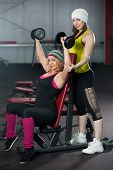 Two Female Partners Train In Gym With Dumbbells