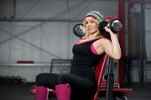 Young Woman Lifts Dumbbells In Gym