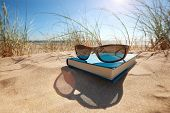stock photo of relaxing  - Book and sunglasses on the beach for summer reading and relaxing - JPG