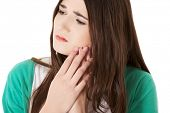 Teen woman pressing her bruised cheek with a painful expression as if she's having a terrible tooth ache.