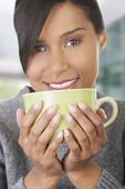 Happy woman drinking cup of tea