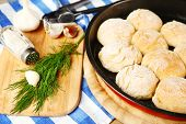 Fresh homemade bread buns from yeast dough on pan and fresh garlic, dill  on cutting board, on color napkin background