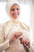 Smiling islamic girl grinding coffee in a hand mill
