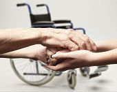 pic of wheelchair  - Hands of an elderly man holding the hand of a younger woman on wheelchair background - JPG