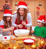 Happy mother with two cute kids wearing red Santa hat cooking festive food on the kitchen, Christmas holidays concept