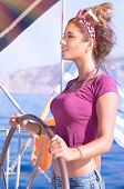 Portrait of beautiful woman sailing, sexy young captain standing behind helm of a sailboat and enjoying bright sun light, summer vacation concept