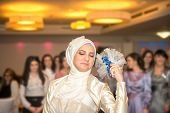 Islamic bride in white dress throws a bouquet of flowers to bridesmaids