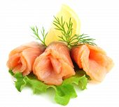 Sliced and rolled salmon  with lemon slice on salad leaf  isolated on white