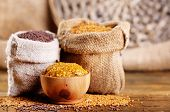 Mustard seeds in bags and sauce in bowl on  wooden background