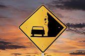Falling rocks warning sign with orange sunrise.