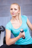Attractive blond sporty girl doing biceps training with a dumbbell