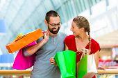 Couple shopping in mall peeking in bags