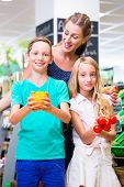 Mother and children selecting vegetables while grocery shopping in organic supermarket