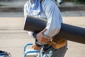 stock photo of thermoplastics  - Man holding Plumbing for connection of plastic pipes - JPG