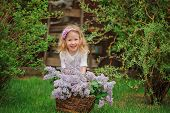 cute happy child girl playing in spring garden with basket of lilacs