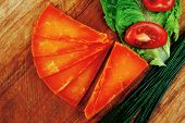 orange aged delicious cheddar cheese chop with slice on wooden plate with tomatoes , chives and salad . isolated over white background
