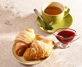 Breakfast with tea, jam and fresh croissants
