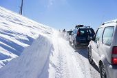 Visitors Waiting Near Their Cars For The Snowmobile To Remove The Snow From The Road In Falakro, Gre