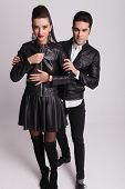 Beautiful fashion woman unzipping her leather jacket while her boyfriend is holding her arms.
