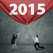 Businesspeople Pulling Number 2015 For Progress