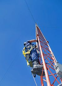 picture of antenna  - Climber on communications  antenna tower with proper safety equipment on - JPG