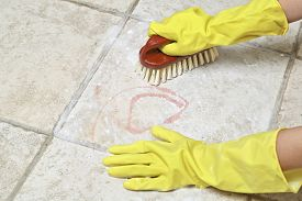 stock photo of scrubs  - hands in rubber gloves scrubbing the tiles - JPG