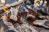 stock photo of log fence  - fireplace and flames on the yard near the fence close up - JPG