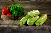 foto of zucchini  - Zucchini tomatoes and parsley on wooden background - JPG