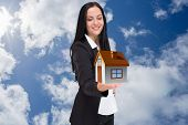 stock photo of presenting  - Pretty businesswoman presenting with hand against bright blue sky with clouds - JPG
