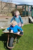pic of wheelbarrow  - Brother and sister playing with a wheelbarrow in their garden - JPG