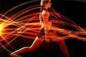 image of light weight  - Fit blonde doing weighted lunges on the beach against curved laser light design in orange - JPG