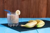 picture of banana  - Healthy homemade Chocolate banana smoothie in glass and fresh bananas on wooden background - JPG
