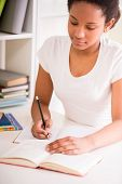 pic of schoolgirl  - Young pretty schoolgirl sitting at the table and writing homework on colorful background - JPG