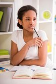 picture of mulatto  - Young pretty mulatto schoolgirl sitting at the table and holding a pencil in hand on colorful background - JPG