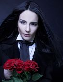 foto of gothic hair  - Romantic portrait of young woman in gothic man image posing with red roses - JPG