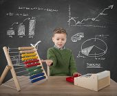 image of kiddie  - Child plays to make calculations with money - JPG
