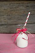 picture of milk glass  - Polka dot straw and white milk in glass retro milk bottle with raffia bow on red and white gingham - JPG