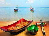 picture of deep  - traditional Vietnam deep fried shrimp and pork rolls in breadcrumbs served on a wood table top by the beach - JPG